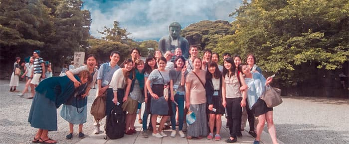photo of group of students in front of statue